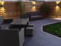 Completed patio with anthracite porcelain flagging and tantalised fencing by night