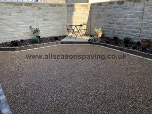 Resin bound patio in Lancaster, Lancashire with flower beds & seating area